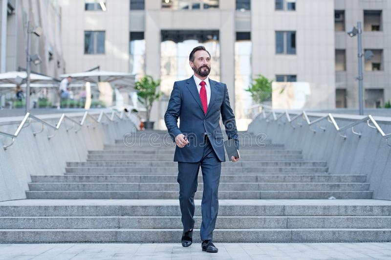 Happy business person walks downstairs in hurry movement with tablet. Young contemporary businessman walking in finance centre royalty free stock photo