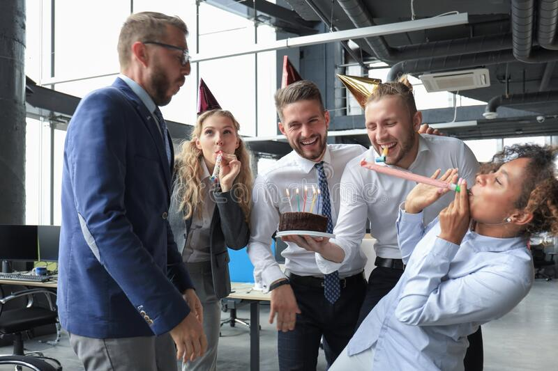 Happy business team with birthday cake are greeting colleague at office party stock images