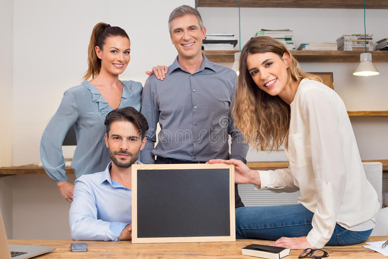 Happy business team with blank sign royalty free stock image