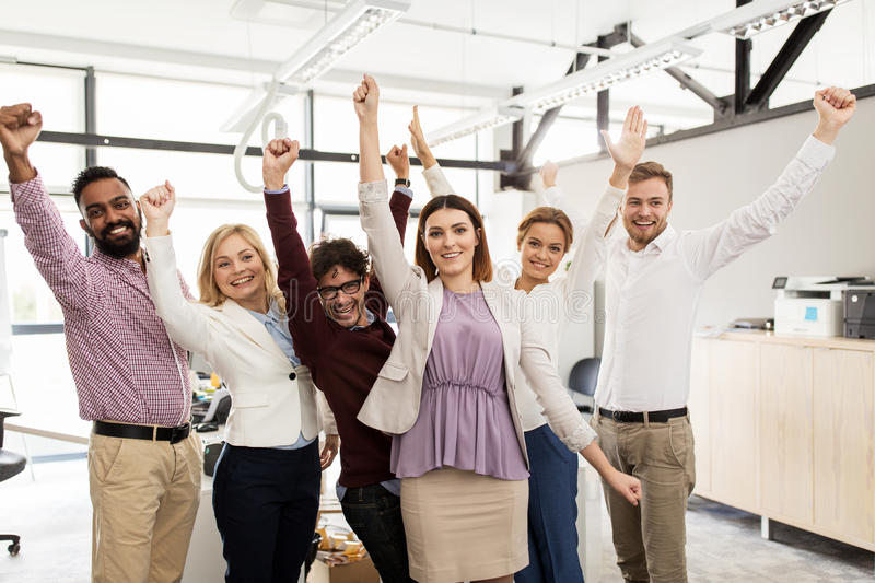 Happy business team celebrating victory at office. Business, triumph, gesture, people and teamwork concept - happy creative team showing fists and celebrating stock photography