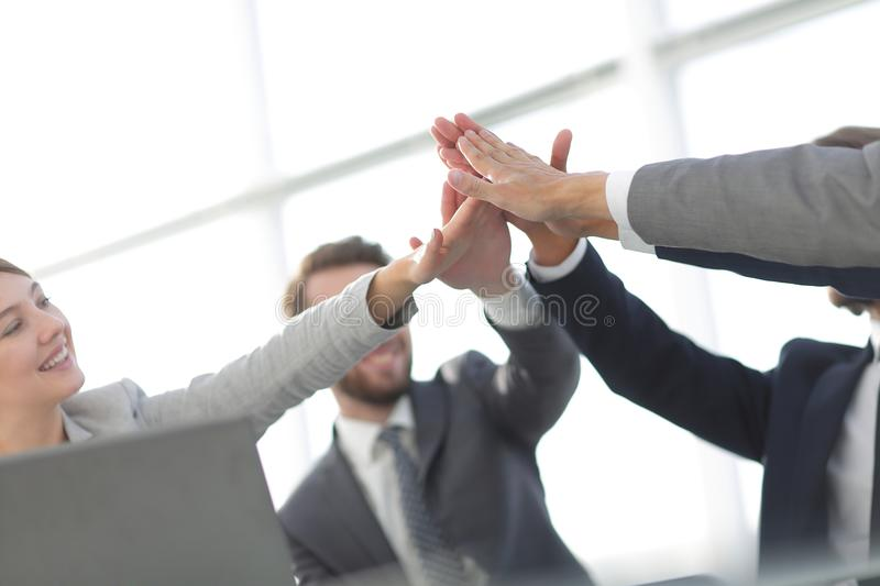 Happy business team giving high five in office royalty free stock images