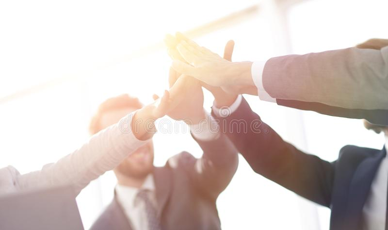 Happy business team giving high five in office. Success and winning concept - happy business team giving high five in office royalty free stock image