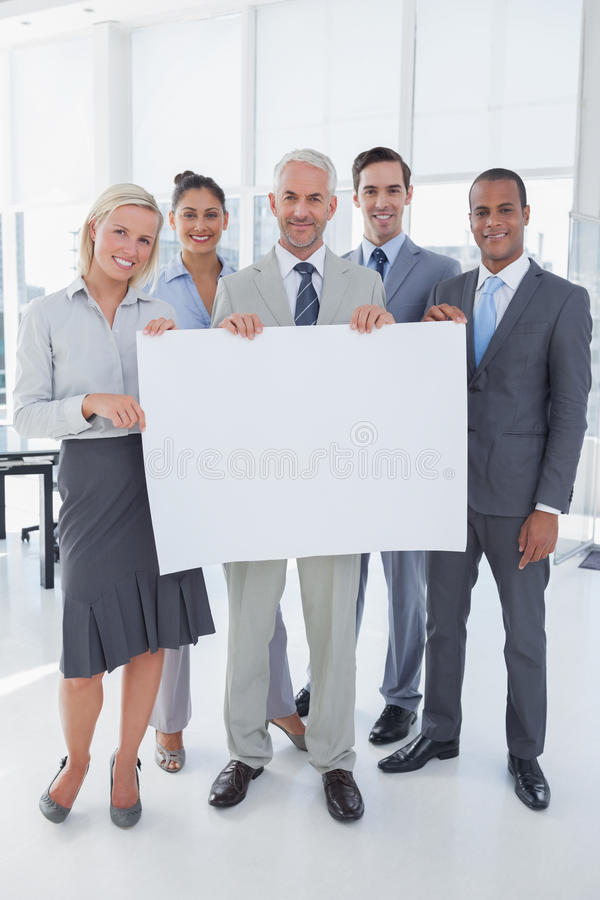 Happy business team holding large blank poster royalty free stock image