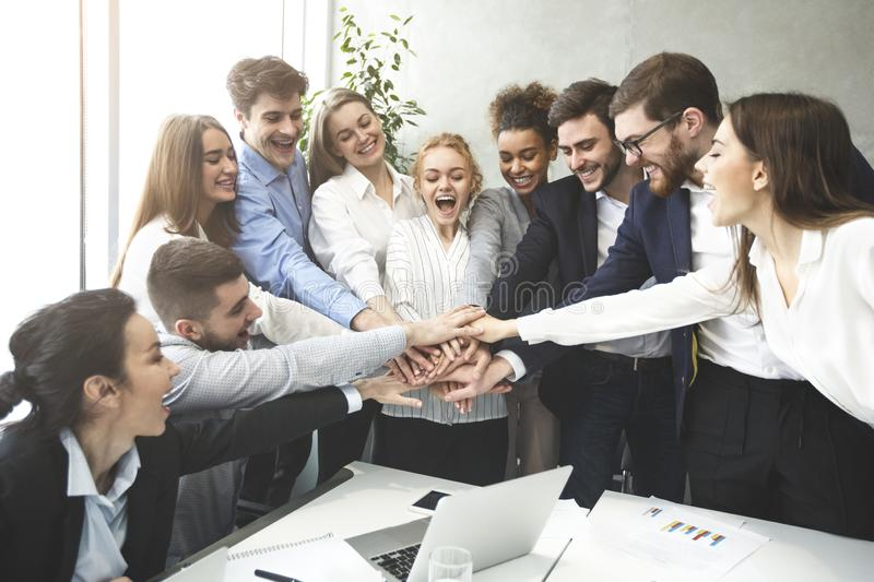 Happy business team joining hands together, celebrating success stock photography