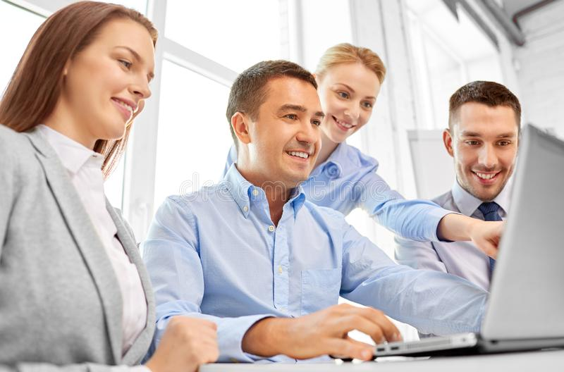 Happy business team with laptop computer in office royalty free stock photo