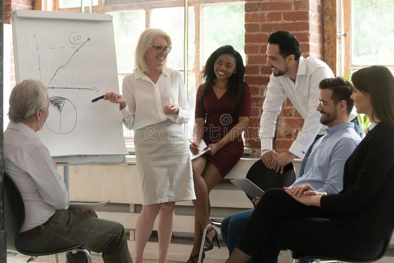 Happy business team listen old mentor give flip chart presentation. Happy business team young employees listen old mature female mentor give flip chart stock photography