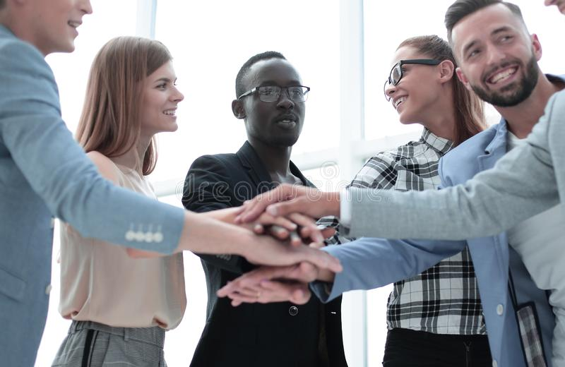 Happy business team makes a tower out of hands. Teamwork, success and celebration concept - happy business team holding hands together at office corporate party royalty free stock image
