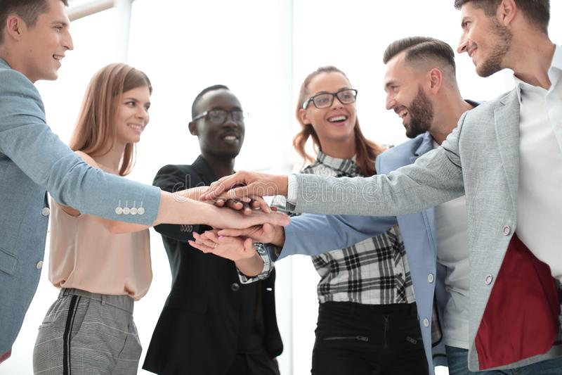 Happy business team makes a tower out of hands. Teamwork, success and celebration concept - happy business team holding hands together at office corporate party royalty free stock photo