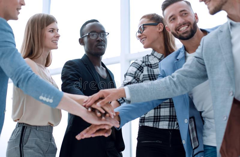 Happy business team makes a tower out of hands. Teamwork, success and celebration concept - happy business team holding hands together at office corporate party royalty free stock images
