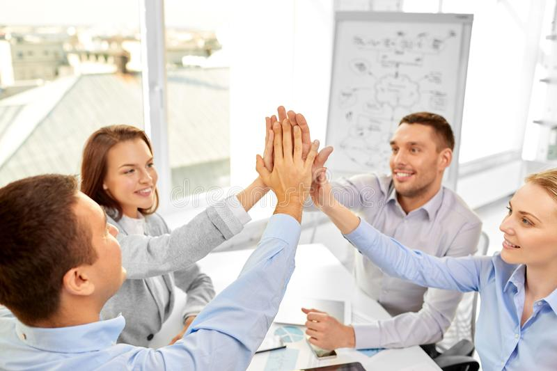 Happy business team making high five at office stock images