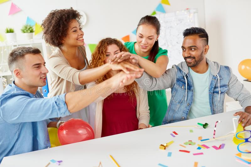 Happy business team at office party holding hands. Teamwork, success and celebration concept - happy business team holding hands together at office corporate stock image