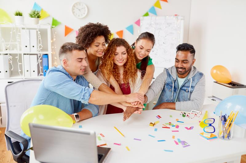 Happy business team at office party holding hands. Teamwork, success and celebration concept - happy business team holding hands together at office corporate royalty free stock images