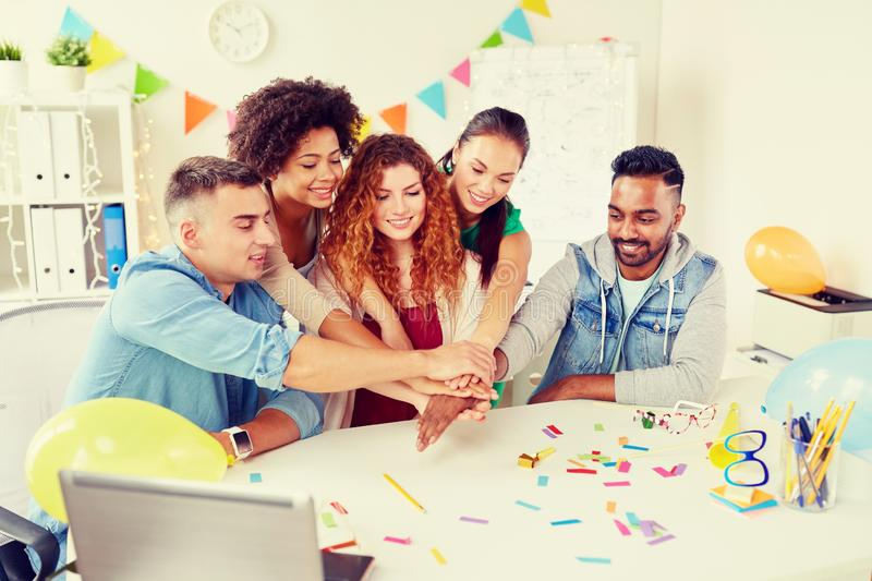 Happy business team at office party holding hands. Teamwork, success and celebration concept - happy business team holding hands together at office corporate royalty free stock photo