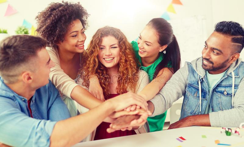 Happy business team at office party holding hands. Teamwork, success and celebration concept - happy business team holding hands together at office corporate stock images