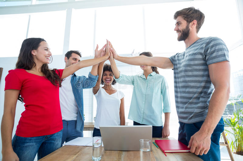 Happy business team putting their hands together stock images