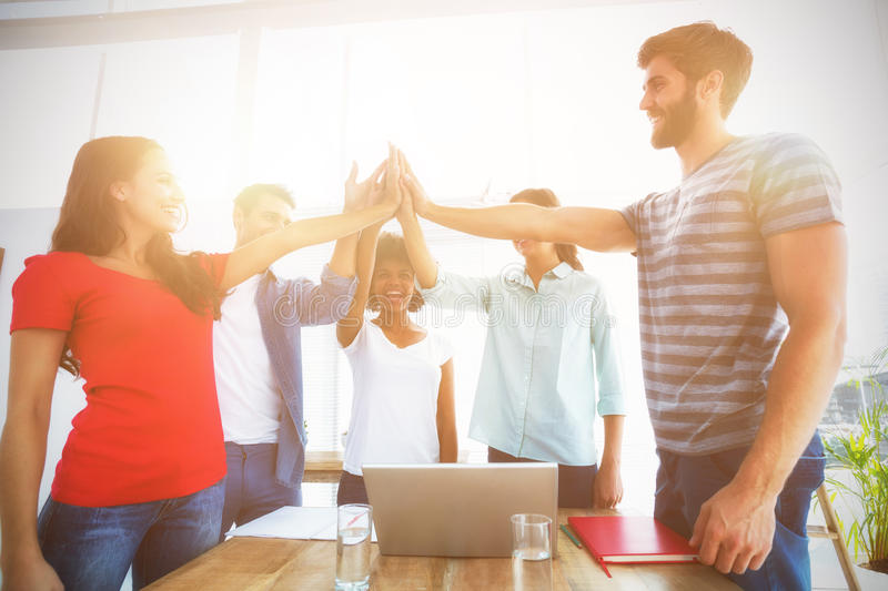 Happy business team putting their hands together. In the office stock photography