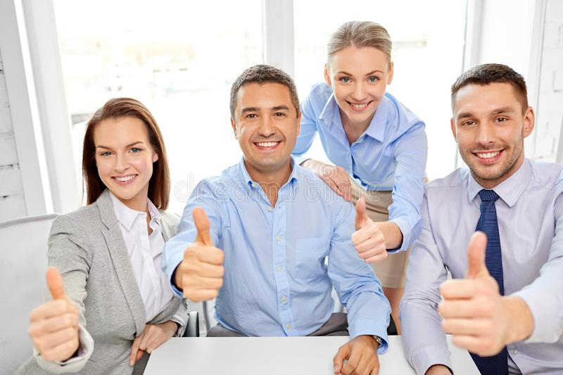 Happy business team showing thumbs up at office stock photography