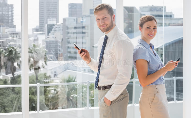 Download Happy Business Team Standing Back To Back And Texting Stock Photo - Image: 32232536