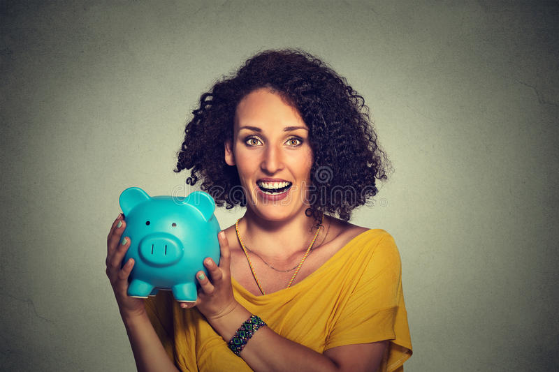 Happy business woman, bank employee holding piggy bank. Closeup portrait happy, smiling business woman, bank employee holding piggy bank, isolated on gray wall stock image