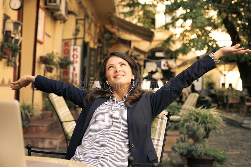 Happy business woman at cafe listening music, arms up. stock image