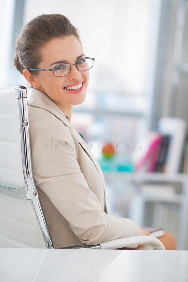 Happy business woman with eyeglasses in office royalty free stock photography