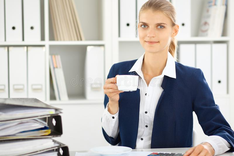 Happy business woman or female accountant having some minutes for coffee and pleasure at working place royalty free stock photo