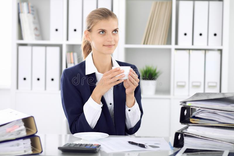 Happy business woman or female accountant having some minutes for time off and pleasure at working place. Audit and tax stock photo