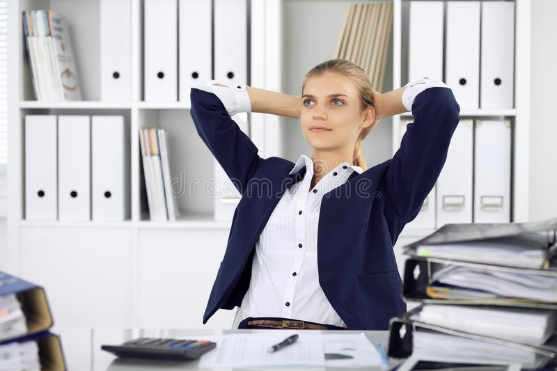 Happy business woman or female accountant having some minutes for time off and pleasure at working place. Audit and tax royalty free stock photo