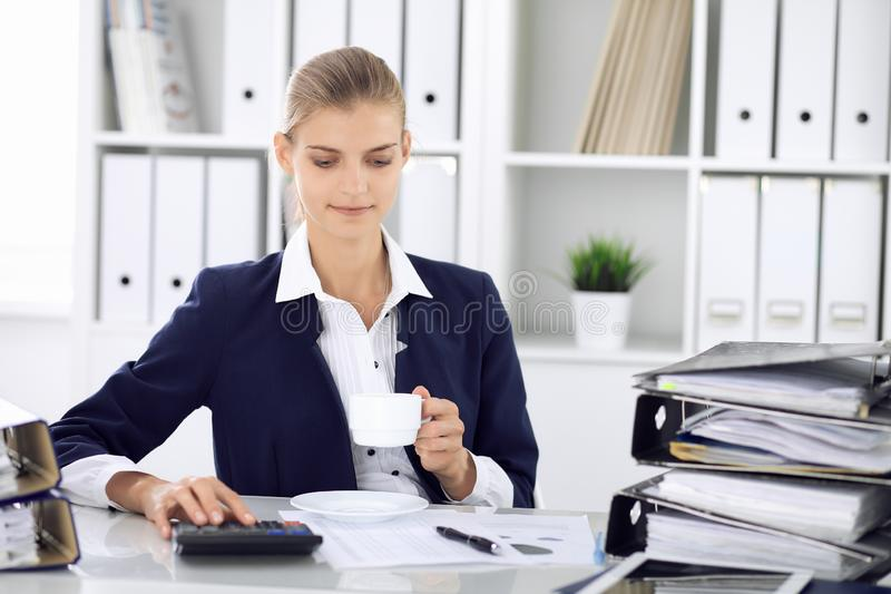 Happy business woman or female accountant having some minutes for time off and pleasure at working place. Audit and tax stock images