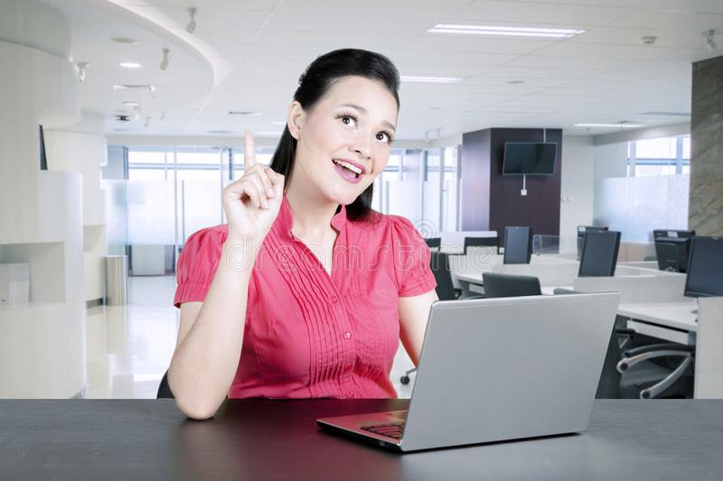 Happy business woman getting an idea while working on laptop computer in office royalty free stock photos