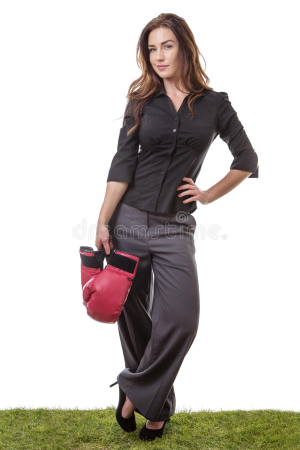 Happy business woman holding boxing gloves. SLim model wearing a business suit, holding some boxing gloves in one hand, standing on grass royalty free stock photos
