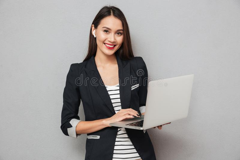 Happy business woman holding laptop computer and looking at camera. Happy asian business woman holding laptop computer and looking at the camera over gray stock photo