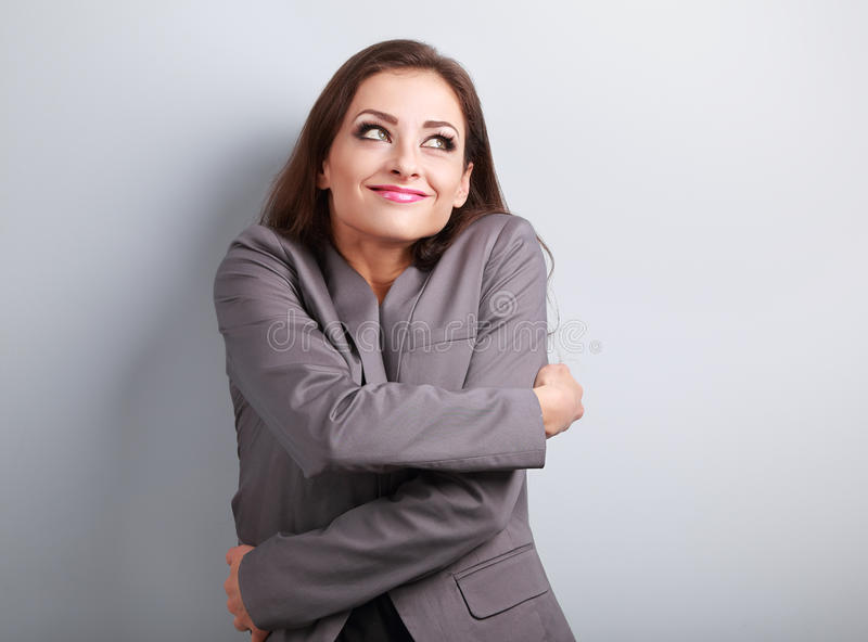 Happy business woman hugging herself with natural emotional enjoying face and thinking look. Love concept of yourself. royalty free stock images