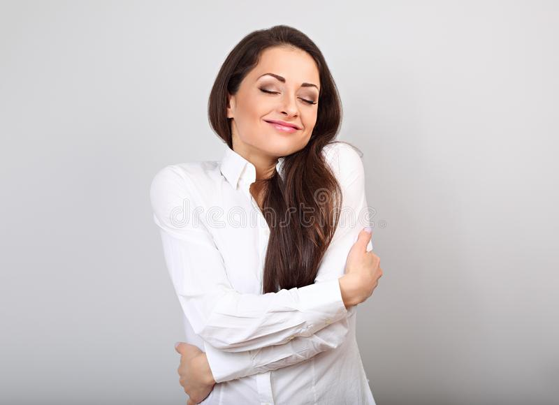Happy business woman hugging herself with natural emotional enjoying face with closed eyes on blue background. Love concept stock image