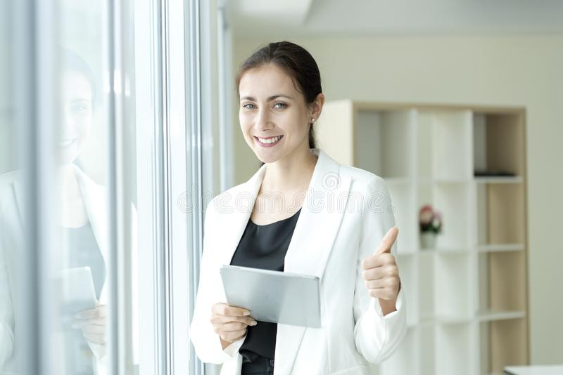Happy business woman looking camera with stance thumb up. Successful concept stock photo