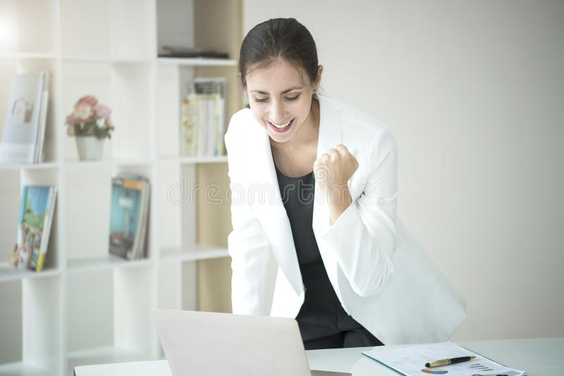 Happy business woman looking computer with arms up. stock photo