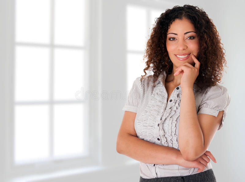 Happy business woman in new office. Beautiful happy smiling corporate executive business woman in her new office in front of windows royalty free stock photos