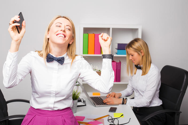 Happy business woman in office cheering. Happy business women in office cheering with phone in her hand stock photo