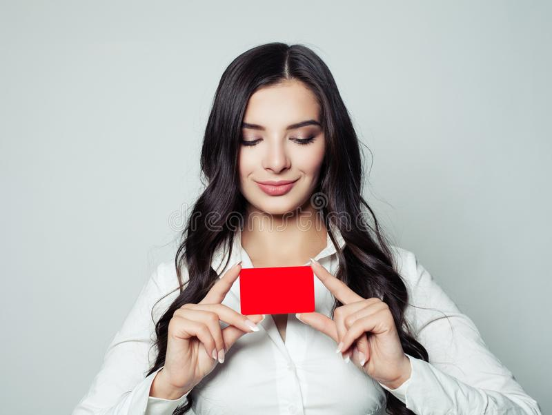 Happy business woman with red empty card. Young woman smiling stock photo