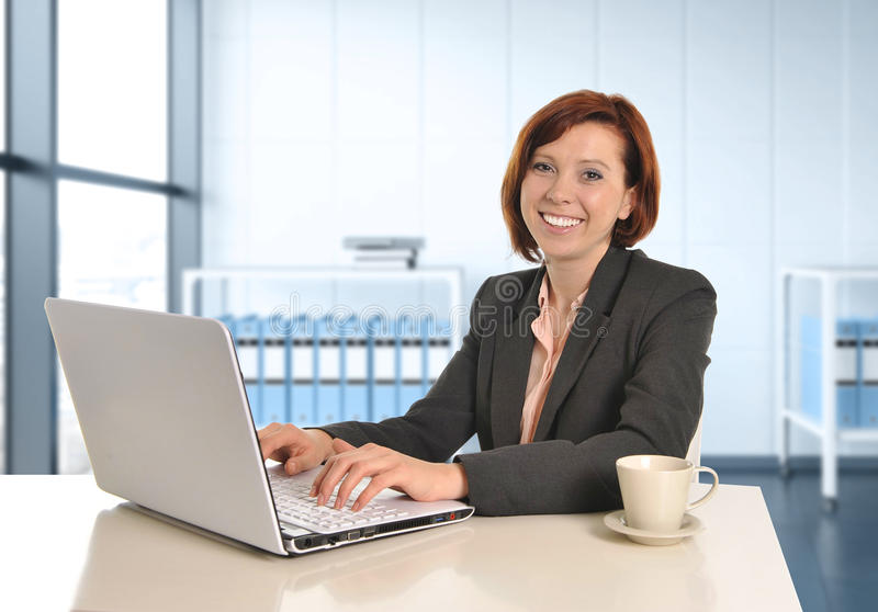 Happy business woman with red hair smiling at work typing on computer laptop at modern office desk stock photography