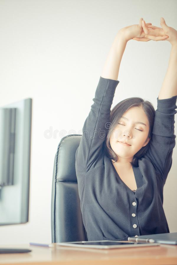 Business woman is relaxing and stretching out in office stock image