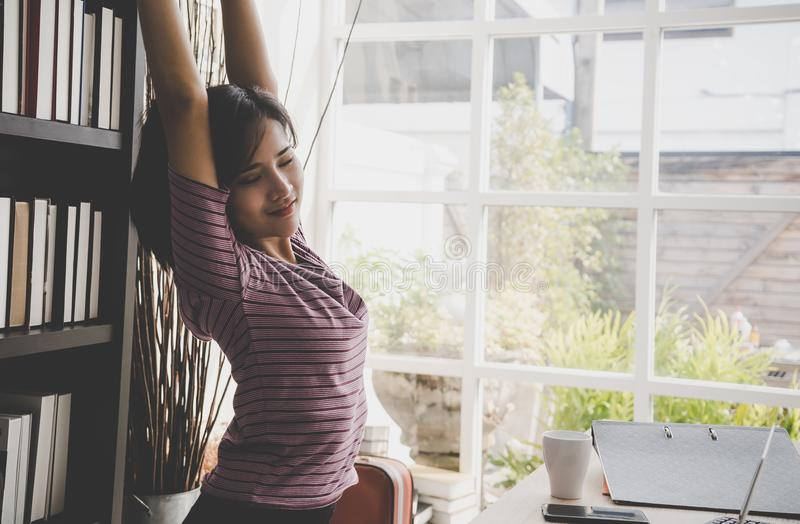 Happy business woman relaxing and stretching out in office royalty free stock photo
