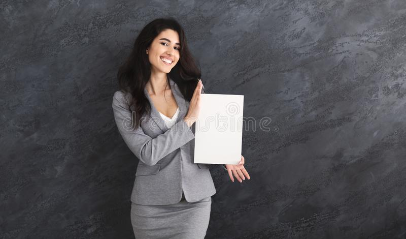 Happy Business Woman Showing Blank Signboard, Grey Wall royalty free stock image