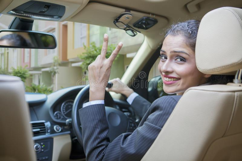 Business woman showing victory sign in a car. Happy business woman showing victory sign at the camera while driving a car stock photos