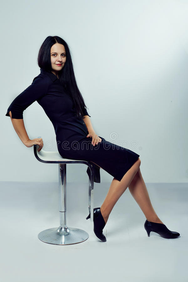 Happy business woman sitting on a chair royalty free stock photography