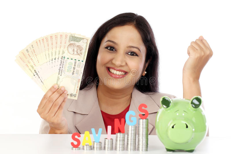 Happy business woman with stack of coins stock image