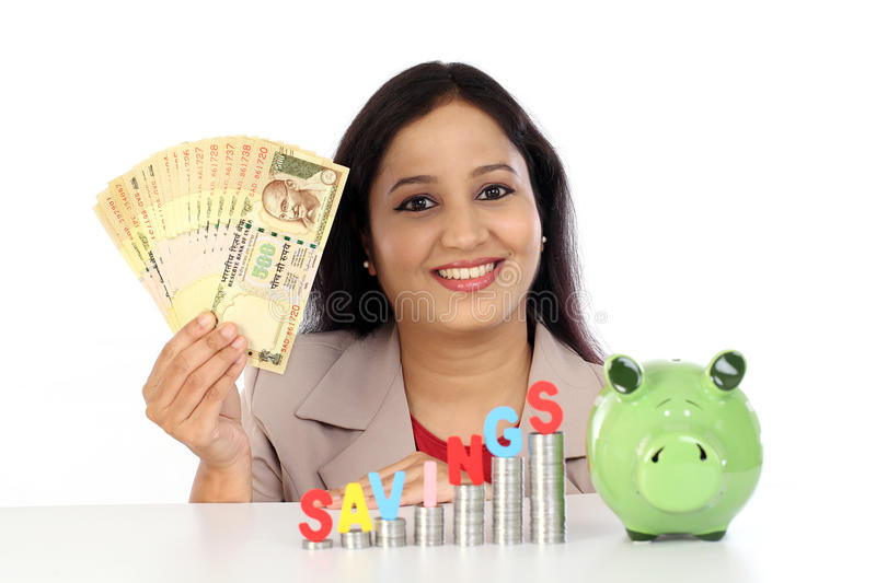 Happy business woman with stack of coins and holding rupee notes stock photos