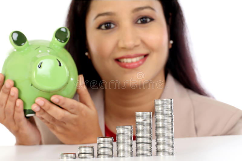 Happy business woman with stack of coins and piggy bank royalty free stock image