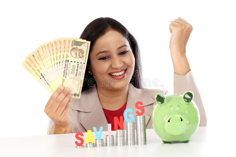 Happy business woman with stack of coins and piggy bank royalty free stock photo