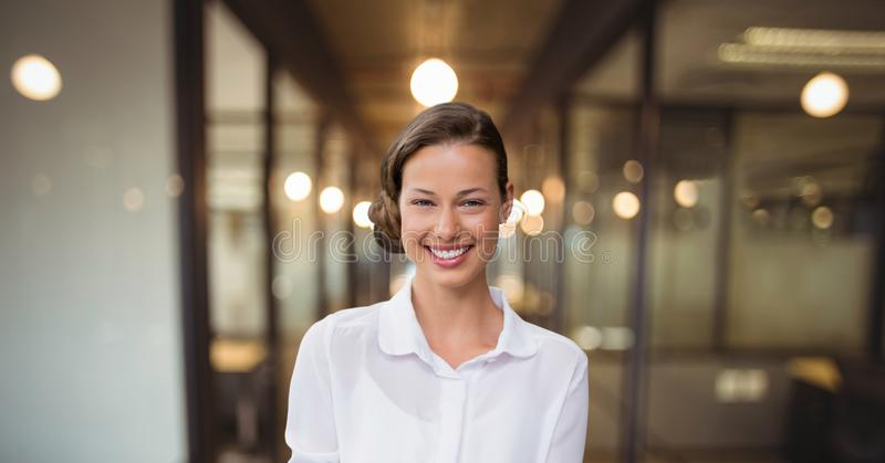 Happy business woman standing against office background stock photos